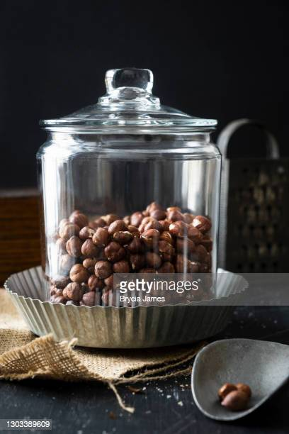 glass canister of shelled hazelnuts on black - brycia james stock pictures, royalty-free photos & images