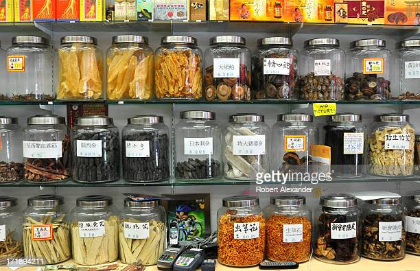 Glass canisters filled with exotic herbs and animal products including deer antlers ginseng and tangerine peelings line shelves in a shop in the...