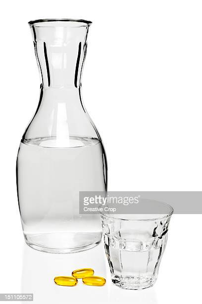 Glass carafe of water with a glass and oil pills