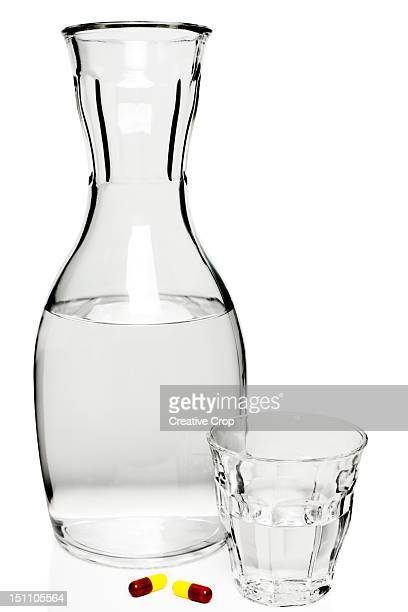 Glass carafe of water with a glass and pills
