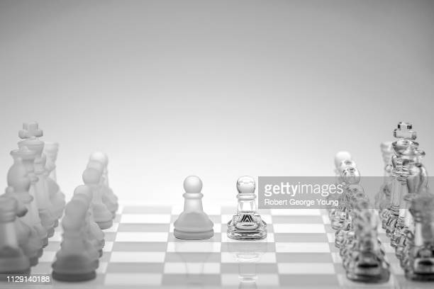 glass chess pieces on a glass chess board featuring opposing pawns - opening event stock pictures, royalty-free photos & images