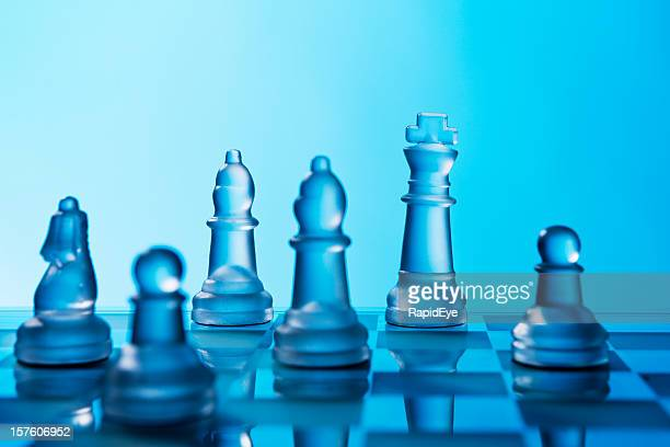 Glass chessmen shine against a blue background