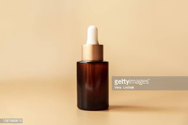 glass cosmetic bottle on brown background. pump bottle, dropper bottle, dispenser cosmetic container flat lay, top view. - brown stock pictures, royalty-free photos & images