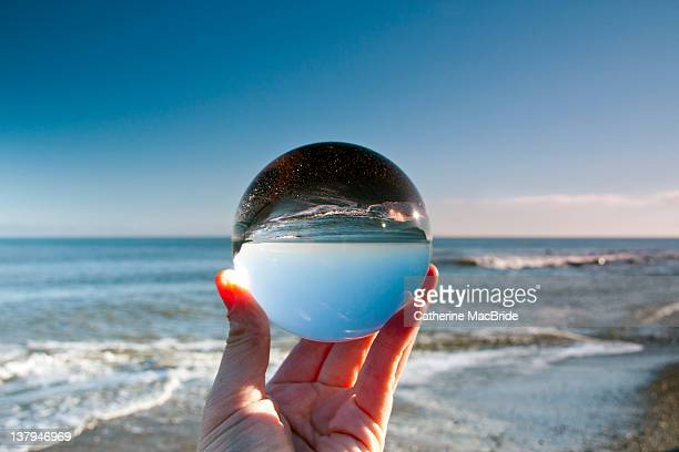 glass crystal ball held up by hand - catherine macbride stock-fotos und bilder