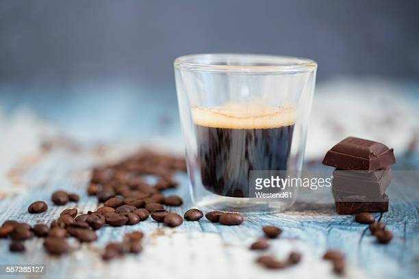 Glass cup of espresso, roasted coffee beans and dark chocolate on wood
