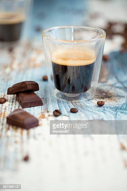 glass cup of espresso, roasted coffee beans and dark chocolate on wood - things that go together stock photos and pictures
