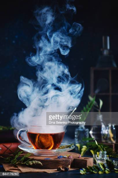 Glass cup of steaming tea with herbs