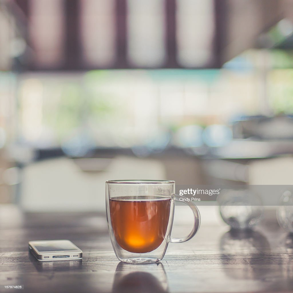 A glass cup of tea and a mobile phone on a table : Stock Photo