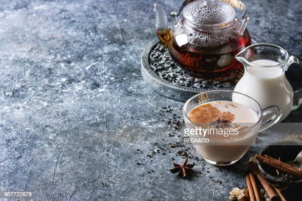 Glass cup of traditional indian masala chai tea with ingredients above Cinnamon cardamom anise sugar black tea in glass teapot jug of milk over dark...