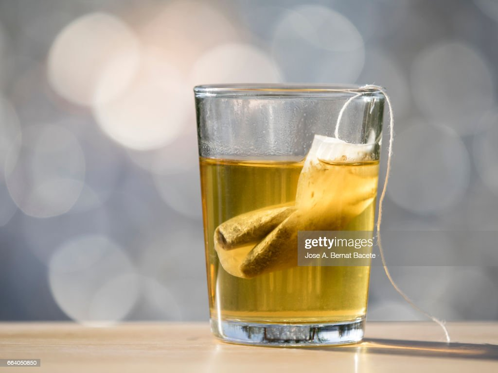 Glass cup on a table to prepare an infusion of grasses of tea (tea bag ),  illuminated by the light of the Sun : Stock Photo