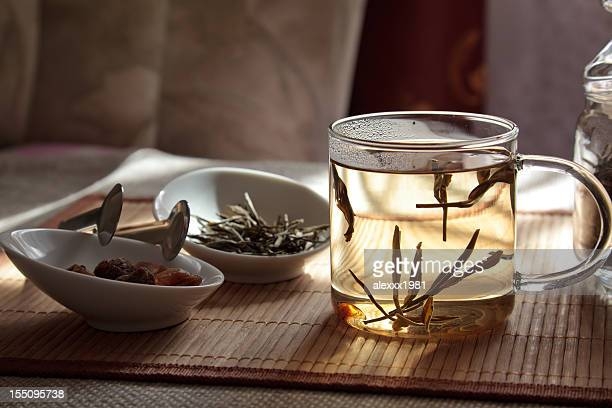 A glass cup with hemp tea and white bowls on a wooden table