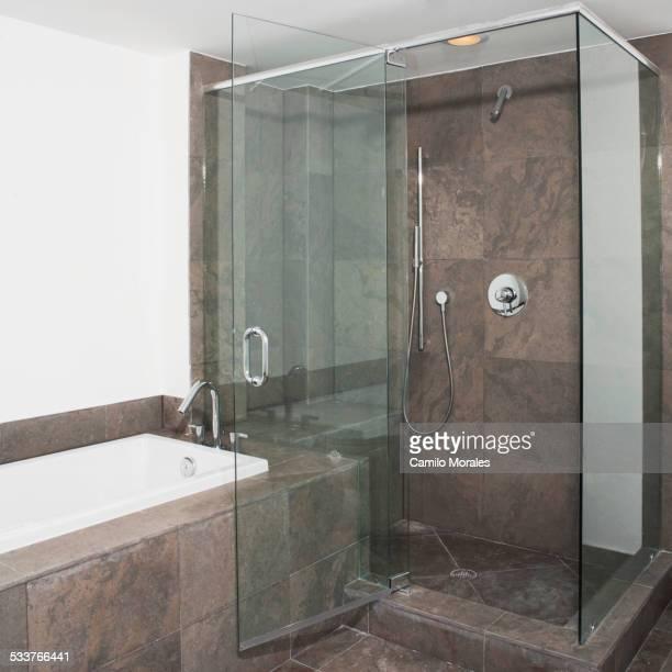 Glass doors of shower and bathtub in modern bathroom