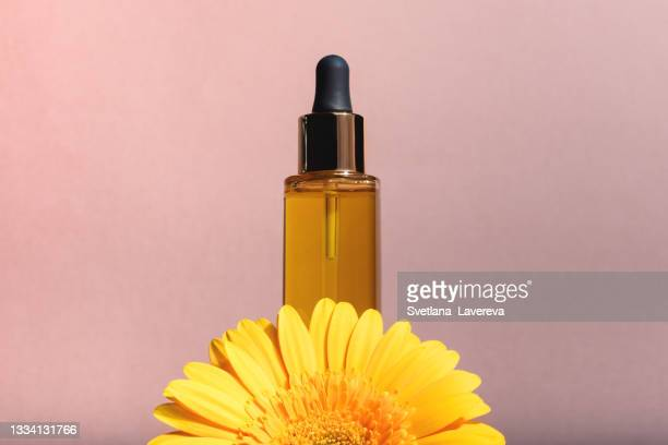 a glass dropper bottle on the beige background. - beauty in nature stock pictures, royalty-free photos & images