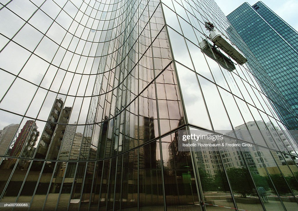 Glass facade of skyscraper with reflections of buildings, low angle view : Stockfoto