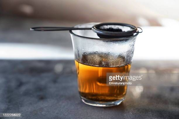glass filled with hot tea from a strainer filled with tea leaves on top on a gray marble tabletop. - emreturanphoto stock-fotos und bilder