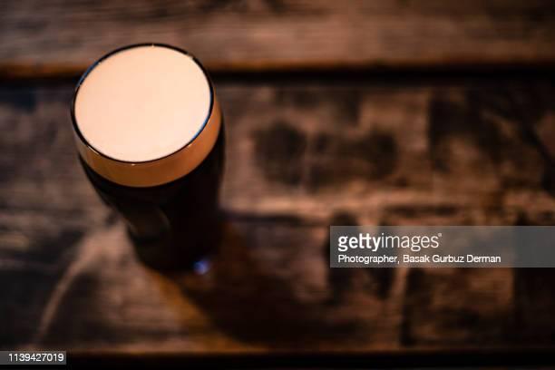 Glass full of dark beer in a pub