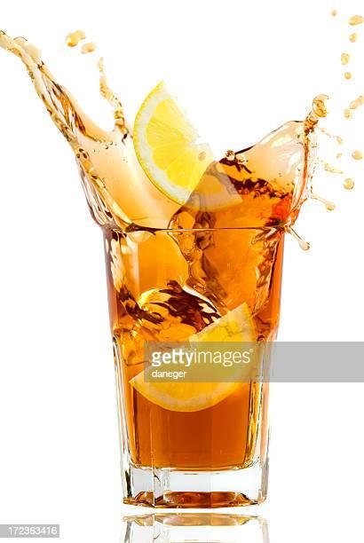 Glass full of fresh iced tea with lemon in artistic splash