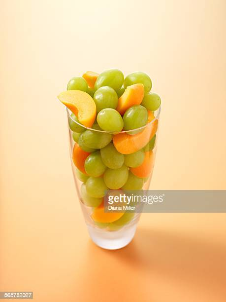 Glass full of grapes and apricot slices on light orange background