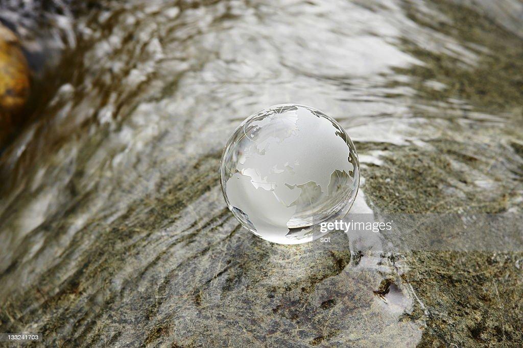 Glass globe on the water stream : Stock Photo