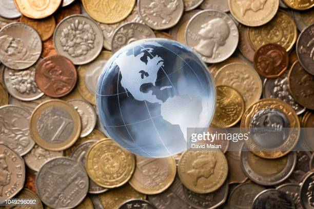 glass globe on top of a layer of coins. - ricchi e poveri foto e immagini stock