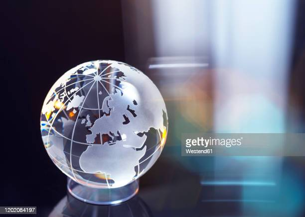 glass globe representing international business and trade - globe stock pictures, royalty-free photos & images