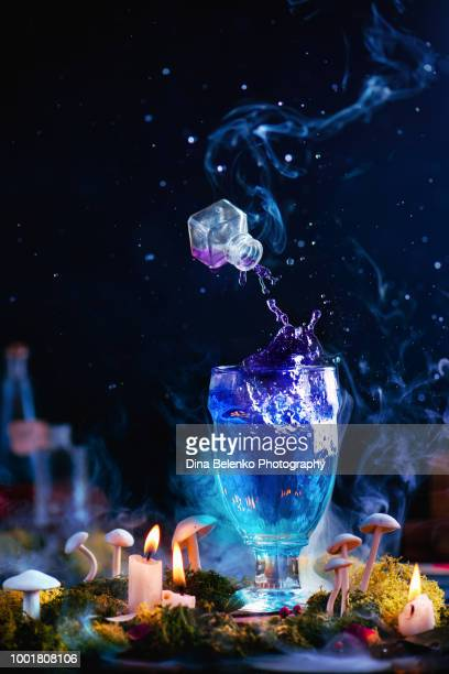 glass goblet with splashing potion and a levitating jar of poison in a dark witchcraft concept. wizard workplace with a magical drink. - potion stock photos and pictures
