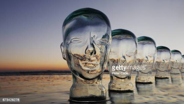 Glass heads on beach at sunset