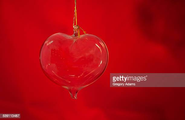 Glass Heart Hanging in Front of a Red Background