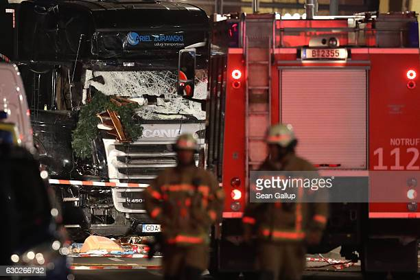 Glass is shattered on the windshield as rescue workers walk near the damaged lorry truck after it was ploughed through a Christmas market on December...