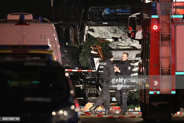 Glass is shattered on the windshield as security and police walk near the damaged lorry truck after it was ploughed through a Christmas market on...