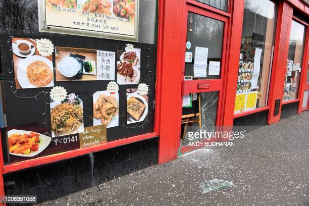 Glass is strewn on the pavement in front of the vandalised door of a Chinese restaurant in Glasgow, Scotland on March 27, 2020. - Britain was under...