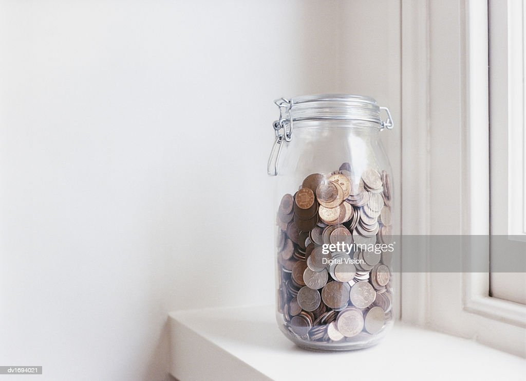 Glass Jar Filled with Coins on a Windowsill : Bildbanksbilder