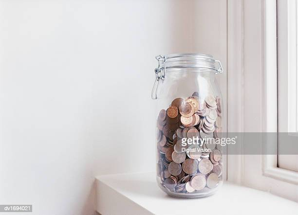 Glass Jar Filled with Coins on a Windowsill