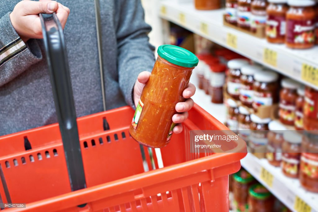 Glass jar of canned vegetables in hands buyer : Stock Photo