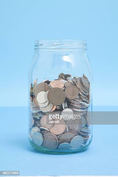 glass jar of coins - jar stock pictures, royalty-free photos & images