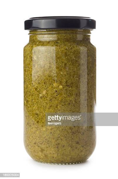 Glass jar of green pesto on a white background
