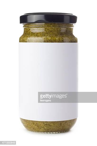 Glass jar of green pesto on a white background