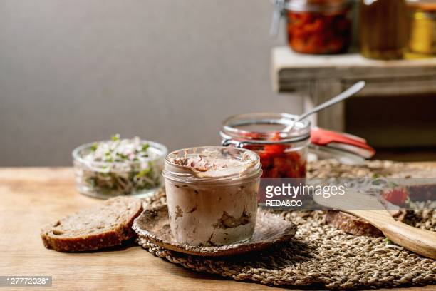 Glass jar of homemade chicken liver pate with sliced rye bread, sun-dried tomatoes and green sprout salad on wooden kitchen table. Home breakfast or...