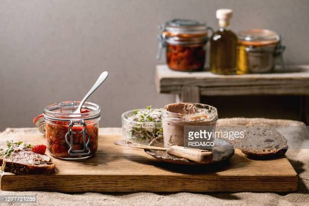 Glass jar of homemade chicken liver pate with sliced rye bread sundried tomatoes and green sprout salad on wooden kitchen table Home breakfast or...