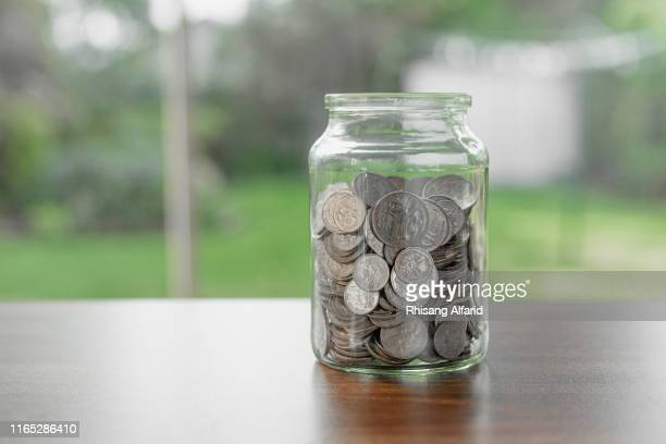 glass jar of silver coins - jar stock pictures, royalty-free photos & images
