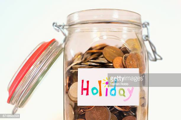 a glass jar of uk coins with a 'holiday' label - jar stock pictures, royalty-free photos & images