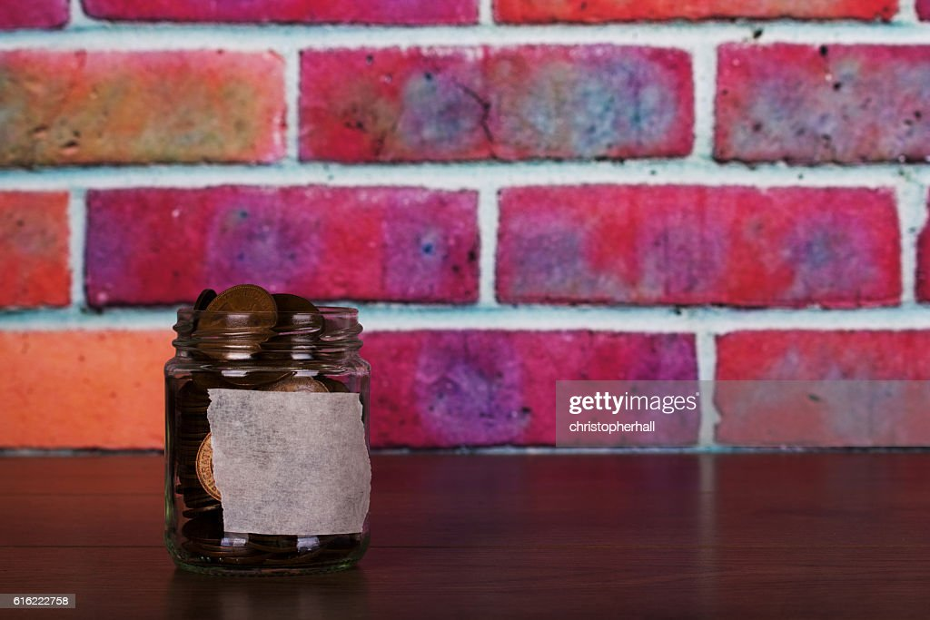 Glass jar on wooden surface filled with old coins : Bildbanksbilder