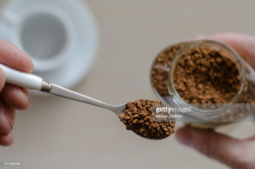 Glass jar with coffee in a hand : Stock Photo