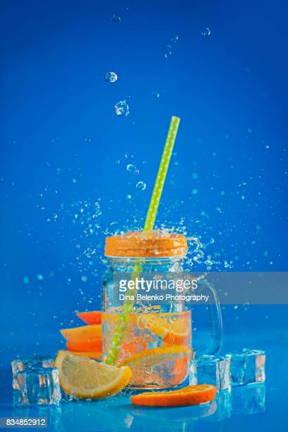 Glass jar with lemonade on a blue background with water spalsch