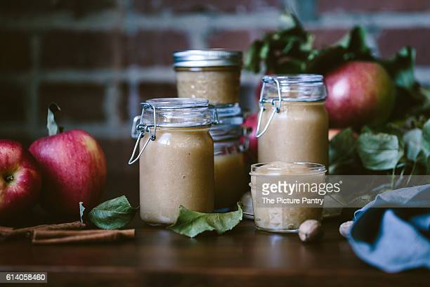Glass jars filled with homemade slow cooker applesauce are photographed from the front view.