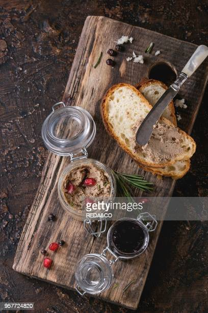 Glass jars of chicken liver pate with blackcurrant jam pomegranate grain and sliced bread served with vintage knife on wooden chopping board over...