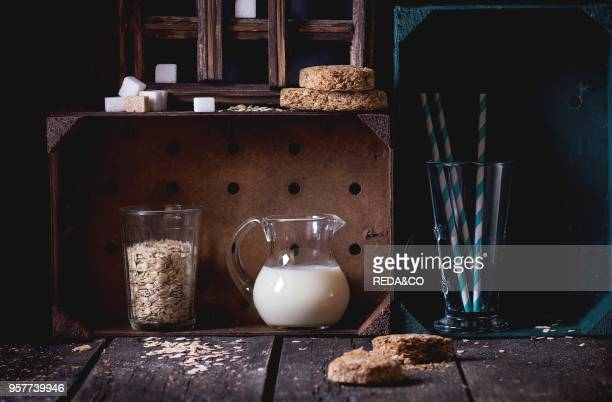 Glass jug of nondairy oat milk and retro glass of oat flakes with sugar cubes and crispbread in wooden kitchen cabinet over old wooden table Dark...