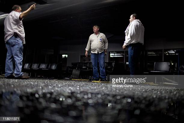 Glass litters the floor of Concourse C as airport maintenance employees inspect damage at LambertSt Louis International Airport's Terminal One after...