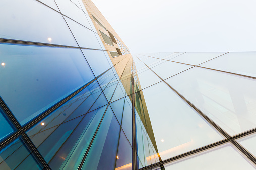 Glass modern building against sky - gettyimageskorea