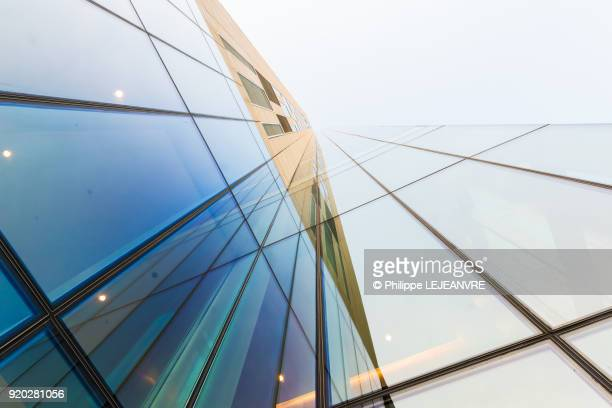 glass modern building against sky - wolkenkratzer stock-fotos und bilder